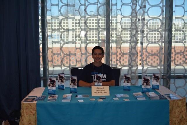 Jonny, a student ambassador, sits at a booth at an event.